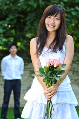 Asian Woman Holding A Bouquet Of Roses With Man Standing Behind