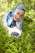 Young woman plucks bilberry in wood