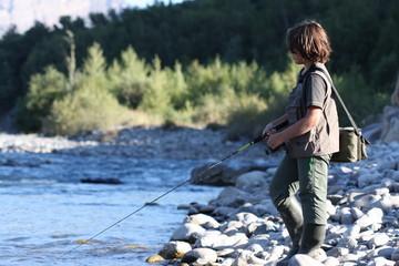 jeune garçon pêchant la truite en rivière