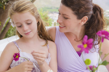 Close-up of a woman smiling with her daughter holding a flower