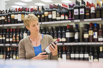 Woman reading a label of a wine bottle