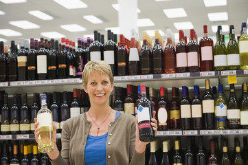 Woman showing two wine bottles in a supermarket
