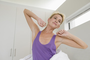 Woman stretching on the bed at morning