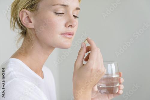Woman taking an Omega-3 capsule