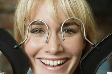 Woman pretending to wear glasses with hanger hook