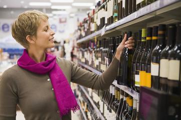 Woman choosing a wine bottle in a supermarket