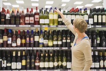 Woman choosing wine bottle in a supermarket