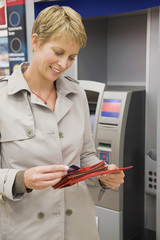 Woman putting a credit card into her wallet and smiling