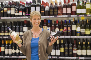 Woman holding two wine bottles in a supermarket