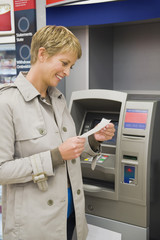 Woman reading a transaction slip at an ATM and smiling