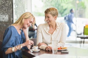 Two women sitting in a restaurant and smiling