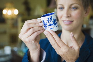 Woman holding a tea cup in a store