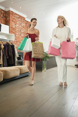 Two women holding shopping bags in a boutique