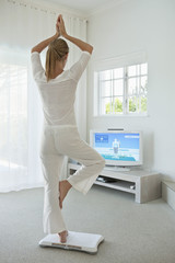 Woman doing yoga in front of television
