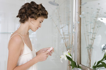 Woman holding contact lens in the bathroom