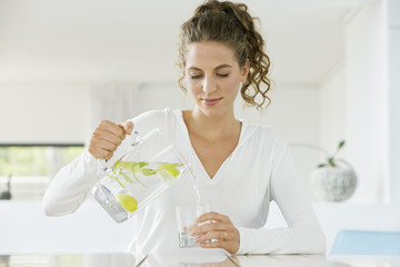 Woman pouring lemonade into a glass from a jug
