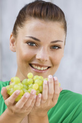 Woman holding bunch of grapes and smiling