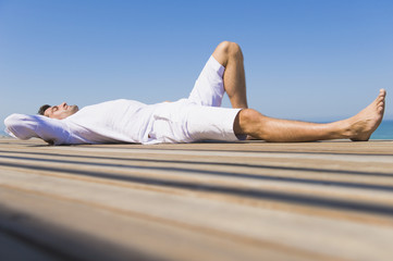 Man lying on a boardwalk on the beach