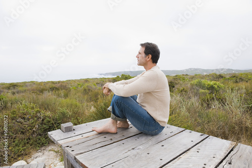 Man sitting on a boardwalk and thinking