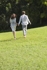 Rear view of a couple running on grass