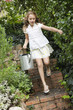 Girl running with a watering can