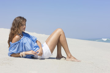 Woman leaning on the beach and thinking
