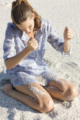 Woman playing with sand on the beach