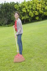 Portrait of a woman raking a lawn