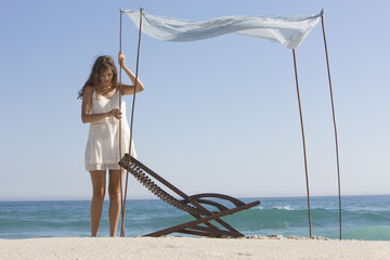 Woman fixing a canopy on the beach