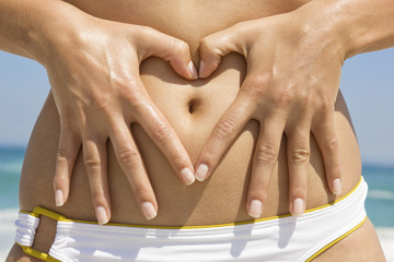 Woman making a heart shape with her finger on her stomach
