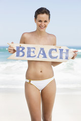 Portrait of a woman covering her breast with a BEACH signboard