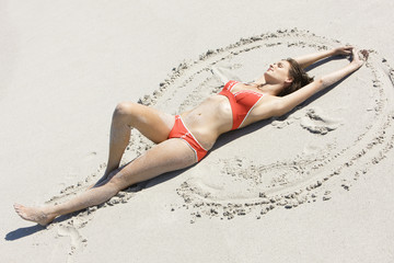 High angle view of a woman making sand angel on the beach