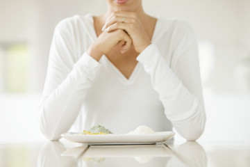 Woman sitting at a table with clays on a plate
