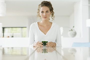 Woman holding a glass of pea soup
