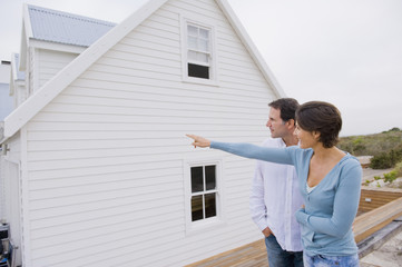 Woman pointing towards a house with a man standing beside her