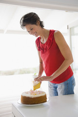 Woman cutting a cake and smiling