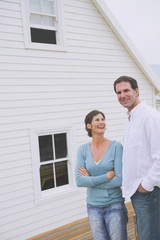 Couple standing together in front of a house