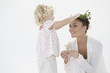 Girl putting a wreath on her mother's head