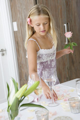 Girl holding a flower and standing at a dining table
