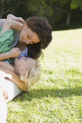 Woman playing with her daughter in a lawn