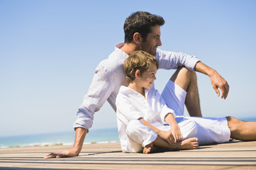 Man sitting on a boardwalk with his son