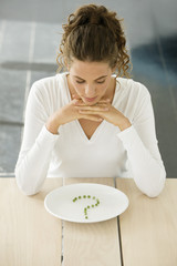 Woman sitting at a table with peas in question mark shape on a plate