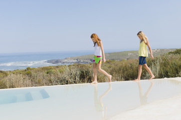 Two girls walking on the ledge of an infinity pool