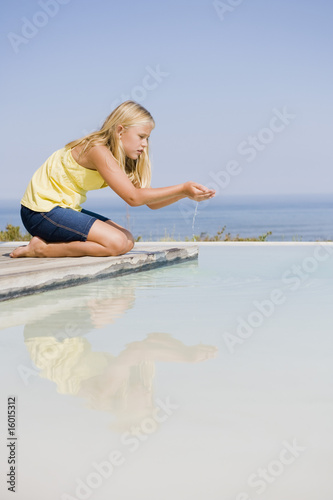 Girl playing on a platform at an infinity pool