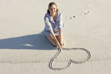 Woman drawing a heart shape on the beach