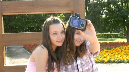 Two happy girls make self-portrait in a park