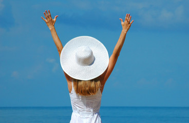 The woman in a white hat with the lifted hands on a beach