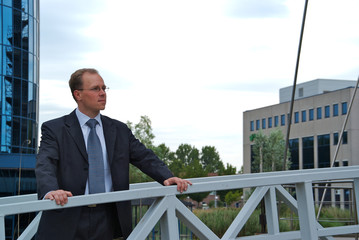 Businessman standing on a bridge