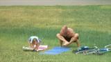 Mature man makes yoga in the park. Girl imitates him. poster