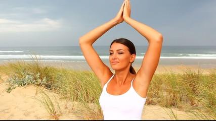 Femme faisant du yoga au bord de l'océan